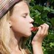 Girl eats red currant in the garden — Stock Photo