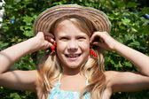 Little girl holding red currants near her ears — Stock Photo