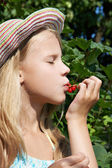 Girl eats red currant in the garden — Photo