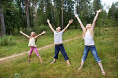 Children on lawn of forest and enjoy life in sports — Stock Photo