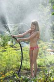 Little girl playing with garden hose — Stock Photo