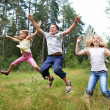 Children jump on lawn in summer forest — Stock Photo