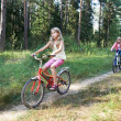 Children riding bikes in woods — Foto Stock