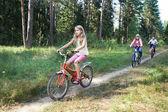 Children riding bikes in woods — Stock Photo