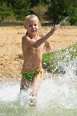 Klein meisje loopt door het water — Stockfoto
