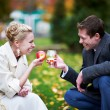 Groom with glass of brandy, and bride with red apple — Stock Photo