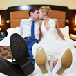 Romantic kiss happy bride and groom in bedroom — Stock Photo
