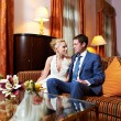 Happy bride and groom in interior of hotel room — Stock Photo
