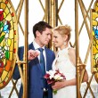 Bride and groom on interior of stained glass window — Stock Photo