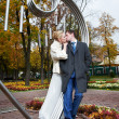 Romantic kiss bride and groom in autumn park — Stock Photo