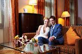 Happy bride and groom in interior of hotel room — Stock Photo