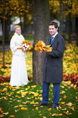 Bride and groom with a maple leaf — Stock Photo