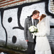 Happy bride and groom kissing near wall with graffiti — Stock Photo