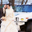 Happy bride and groom about wedding limousine — Stock Photo