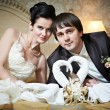 Handsome bride and groom in bedroom with towels swans — Stock Photo