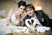 Handsome bride and groom in bedroom with towels swans — Foto de Stock