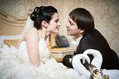 Handsome bride and groom in bedroom — Stock Photo