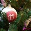 Christmas ball with painted gift — Stockfoto