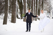 Happy bride and groom running in winter park — Stock Photo