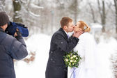 Operator shooting romantic kiss happy bride and groom — Stock Photo