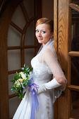 Happy beautiful bride with bouquet near doors — Stock Photo