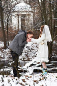 Groom kissing bride's hand in the winter woods — Stock Photo