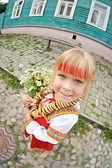 Russian girl in national costume with bagels and flowers — Stock Photo