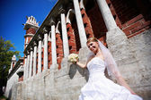 Happy Bride at wall to palace — Stockfoto