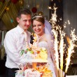 Stok fotoğraf: Bride and groom at wedding cake with fireworks
