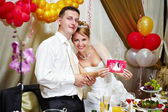 Bride and groom show a greeting card — Stock Photo