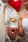 Candle in hands of newlyweds — Stock Photo