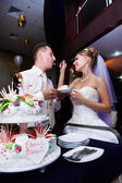 Bride feeding her fiance wedding cake — Stock Photo