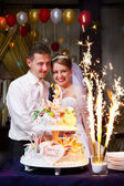 Bride and groom at the wedding cake with fireworks — Stock Photo