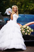 Happy bride near wedding car — Stock Photo