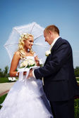 Happy bride and groom on background blue sky — Stock Photo