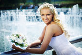 Happy bride with bouquet of flower near fountain — Stock Photo