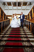 Elegant bride and groom in luxury stairs with red carpet — Stock Photo