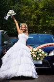 Happy bride with bouquet near wedding car — Stock Photo