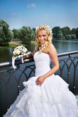 Happy bride with bouquet of flower near lake — Stock fotografie