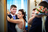 Happy bride and groom in wedding day near mirror — Stock Photo