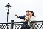 Bride and groom around the fence of the bridge — Stock Photo
