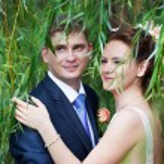 Happy bride and groom near willow tree — Stock Photo