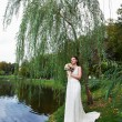 Beautiful bride near lake in autumn park — Foto de Stock