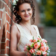 Happy bride with wedding bouquet about brick wall — Stock Photo #40864957