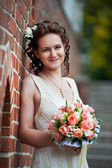 Happy bride with wedding bouquet about brick wall — Stock Photo