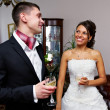 Happy bride and groom with glasses of champagne — Stock Photo