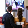 Stock Photo: Bride and groom watch video of his wedding