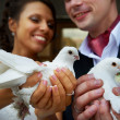 Bride and groom with pigeons in his hands — Stock Photo