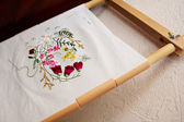 Wooden frame and fabric with embroidery — Stock Photo