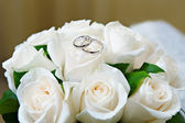 Gold wedding rings on the flower rose — Stock Photo